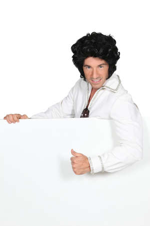 Man in an Elvis outfit and a board left blank for your image Stock Photo - 17506357