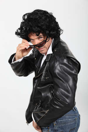 Man wearing leather jacket, sunglasses and wig photo