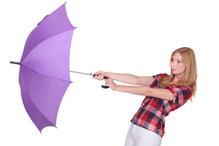 blown away: Woman and her umbrella being swept away by the wind