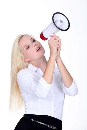 loudhailer: Blond woman speaking into megaphone Stock Photo