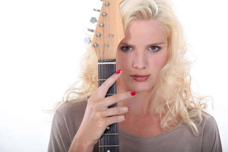 impassive: Woman holding an electric guitar Stock Photo