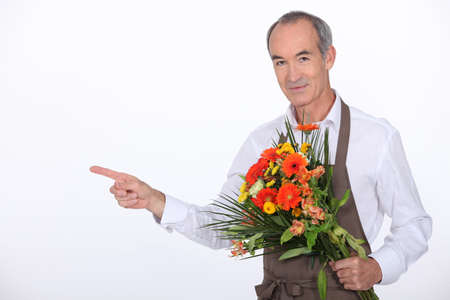 65 years old: 65 years old male florist taking a flowers bouquet and pointing finger on something