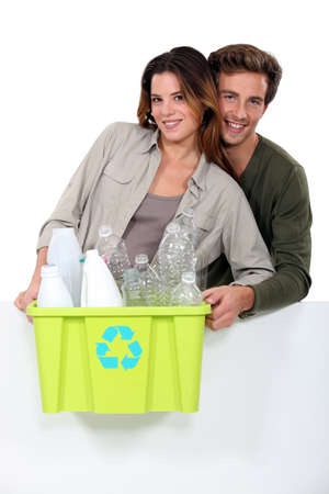 Smiling couple sorting garbage on white background photo