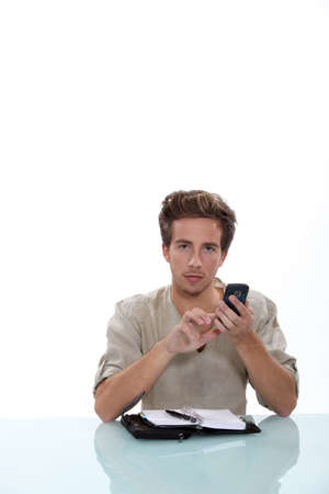 Man sitting a desk with a cellphone and personal organizer photo