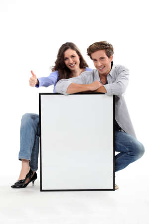 Couple crouching by empty frame Stock Photo - 17579695