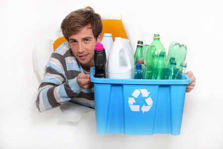 Young man holding a recycling bin photo