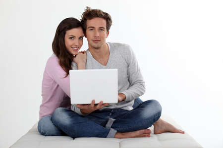 clothed: Couple using a laptop on a bed