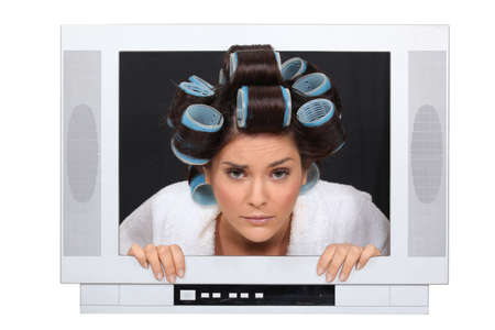 Woman in hair rollers trapped in television Stock Photo - 17584477