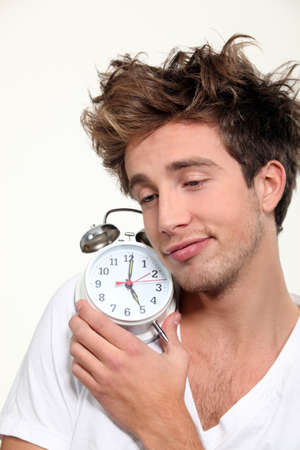 slumberous: Sleepy man hugging his alarm clock