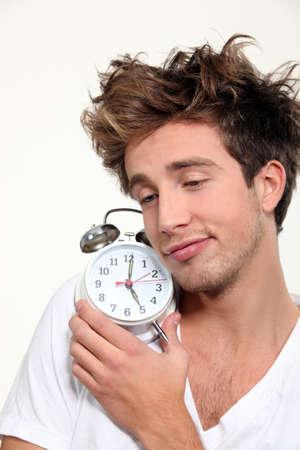 Sleepy man hugging his alarm clock