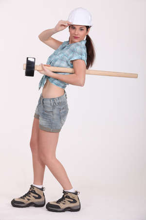 sledge hammer: A female construction worker with a sledgehammer.