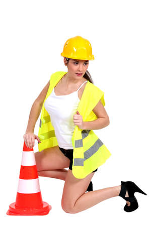 kneel down: portrait of sexy female builder with construction cone