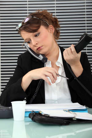 burdened: Secretary burdened with two phones Stock Photo
