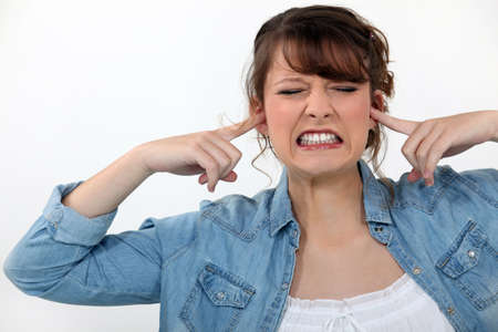 intolerable: Woman covering her ears