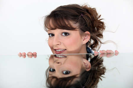 grabbing at the back: Face of woman reflected in mirror Stock Photo