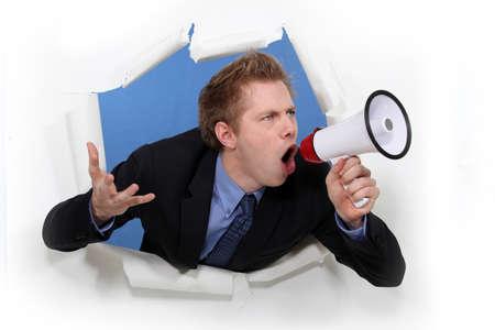 speaking tube: Angry businessman shouting through megaphone Stock Photo