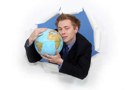 Businessman hugging globe photo