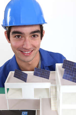 portrait of young bricklayer posing near model photo