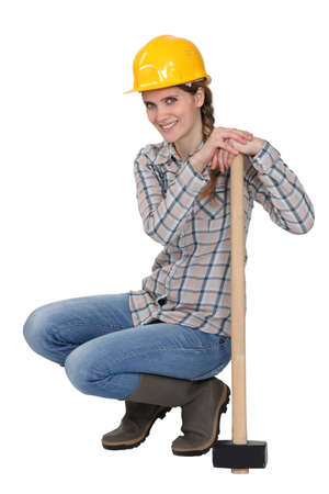 servicewoman: cCrouching with sledge hammer Stock Photo