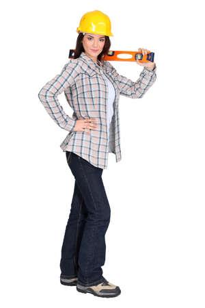 yourselfer: Brunette holding spirit-level Stock Photo