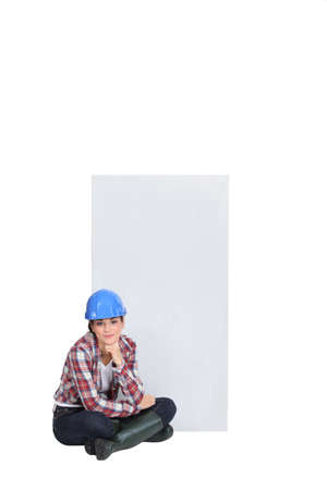 Female construction worker sat on the floor thinking Stock Photo - 17577494