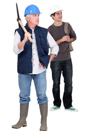 senior bricklayer and junior apprentice against studio background photo