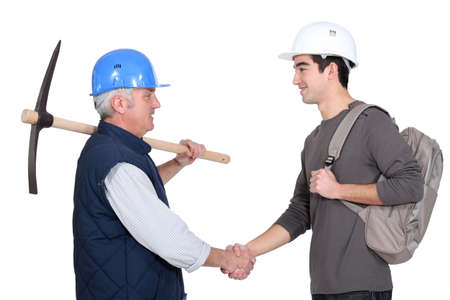 manly man: A construction worker and his trainee shaking hands.