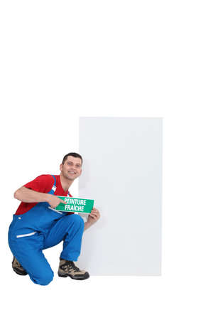 craftsman holding a wet paint caution board Stock Photo - 17577481
