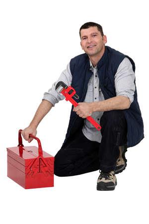 toolset: Plumber kneeling by tool-box