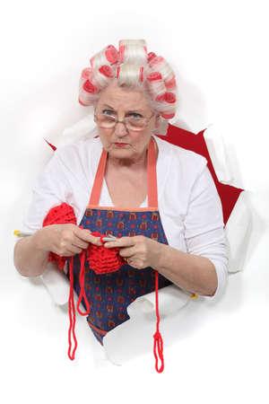 grumpy: Oma met haar haar in rollen en breien Stockfoto