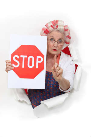 impede: Granny holding a stop sign and with her hair in rollers
