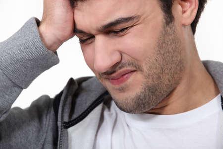 throb: Man suffering from a throbbing headache