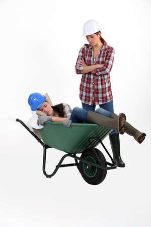 tradeswomen: Construction worker discovering her colleague fast asleep Stock Photo