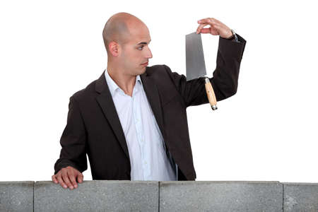 sideway: Businessman looking at a trowel.