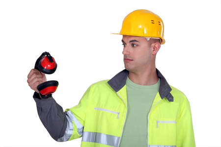 unskilled worker: Construction worker staring at his earmuffs