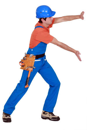 protective workwear: Tradesman pushing empty copyspace Stock Photo