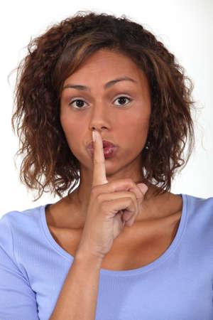 shushing: Woman shushing. Stock Photo