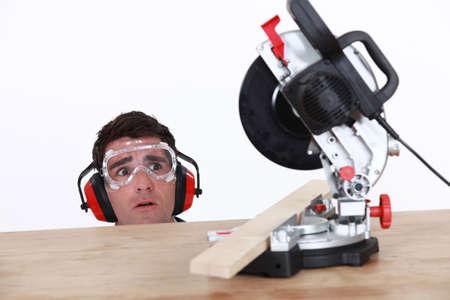 A carpenter afraid of his circular saw  photo