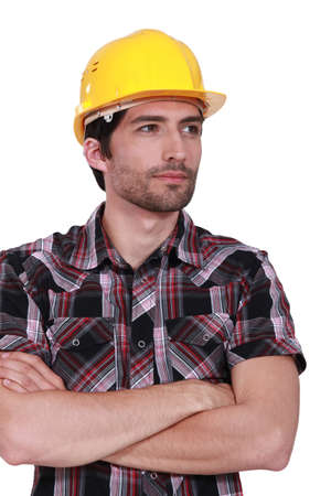 cross armed: portrait of handsome craftsman with safety helmet standing cross-armed