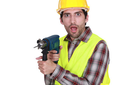 A man holding a drill with a weird facial expression  Stock Photo - 17732463