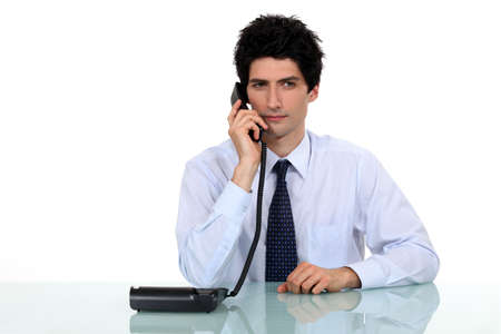 Businessman making call on land-line telephone photo