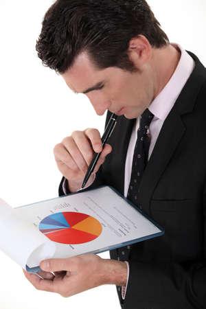 interpret: Man examining pie-chart Stock Photo