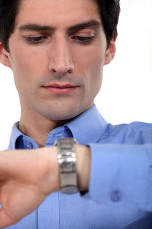 wasting: Young businessman checking the time Stock Photo