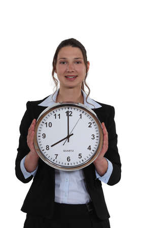woman in a suit holding a huge clock photo