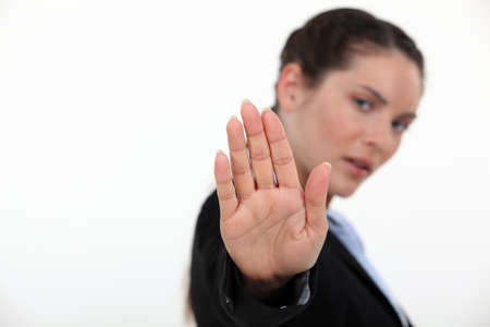 impede: Businesswoman holding her hand up