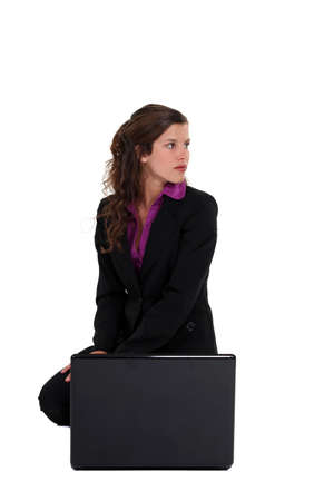 attractive young businesswoman crouching with laptop photo