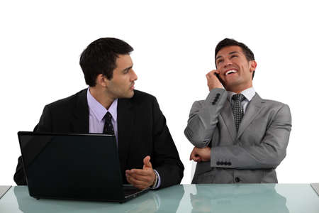 Businessman getting annoyed at loud colleague photo