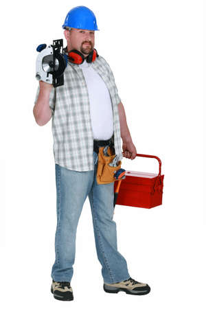 Tradesman holding a circular saw and his toolbox photo