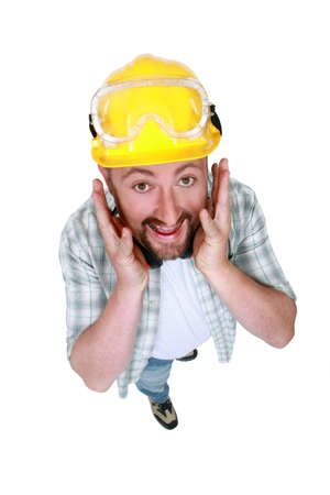 Goofy tradesman putting his hands along his face photo