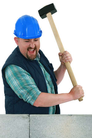 Man about to smash a wall using a mallet photo